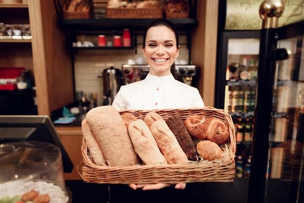 パン屋さんでパンと立っている若い笑顔の女性。 Premium写真