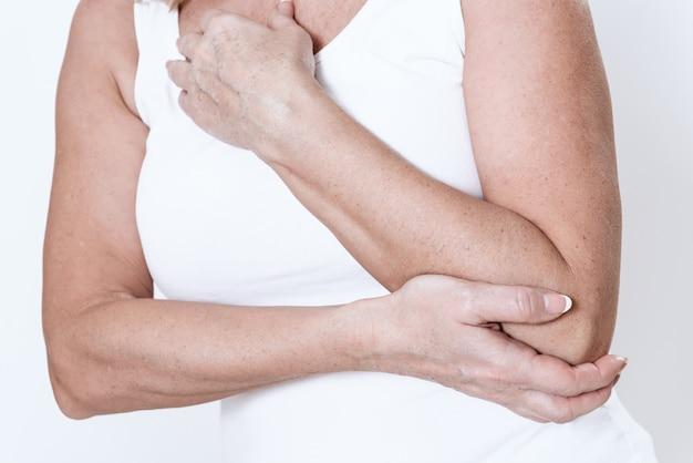 女性は腕に痛みがあります。彼女はそれにしがみつきます。 Premium写真