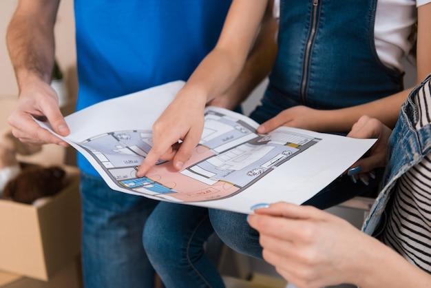 幸せな家族は、家の設計図の部屋のレイアウトを勉強しています。 Premium写真