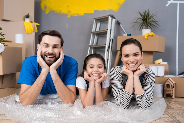 Семья лежит на пузырчатой пленке и планирует сделать ремонт в доме Premium Фотографии