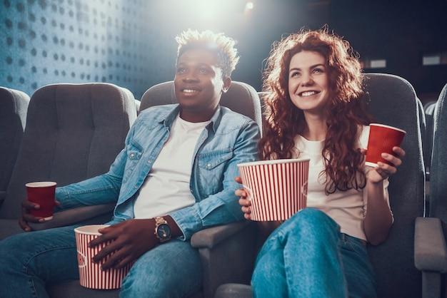 映画館にポップコーンと若いカップルが座っています。 Premium写真