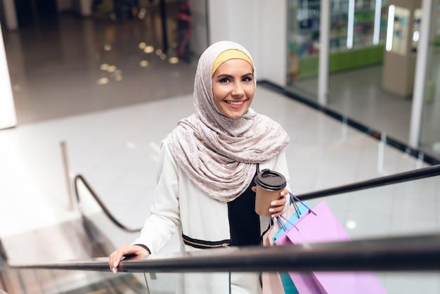 モールに立っているコーヒーのカップを持つアラビアの女性。 Premium写真