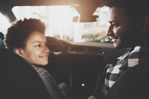 お父さんと子供が前の席に座って車を買う。 Premium写真