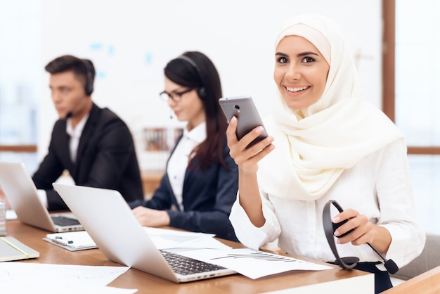 ヒジャーブを着たアラブの女性が電話を見ます。 Premium写真
