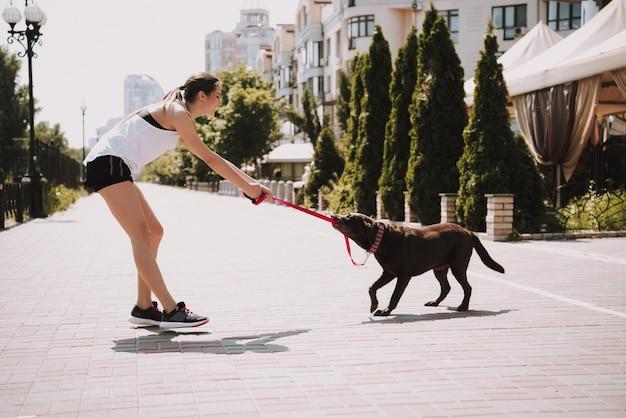 Спортсменка играет с собакой на городской набережной Premium Фотографии