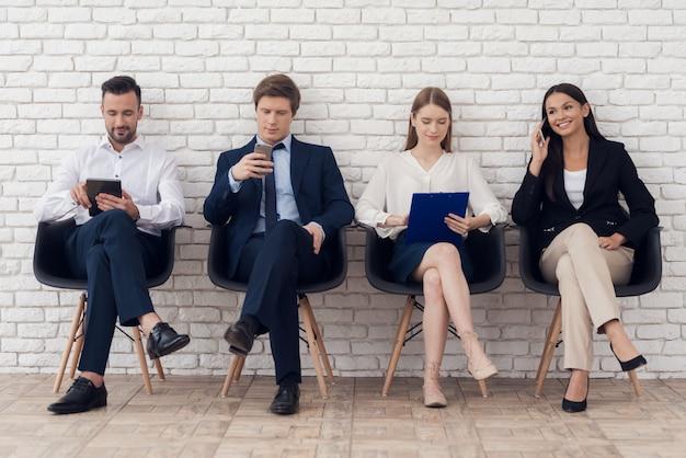 Молодые коллеги в элегантных костюмах сидят на черных стульях. Premium Фотографии