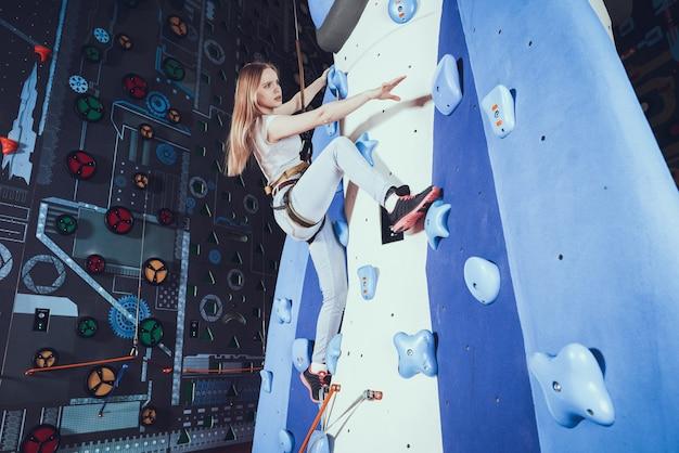 屋内で岩壁にロッククライミングの練習の若い女性。 Premium写真