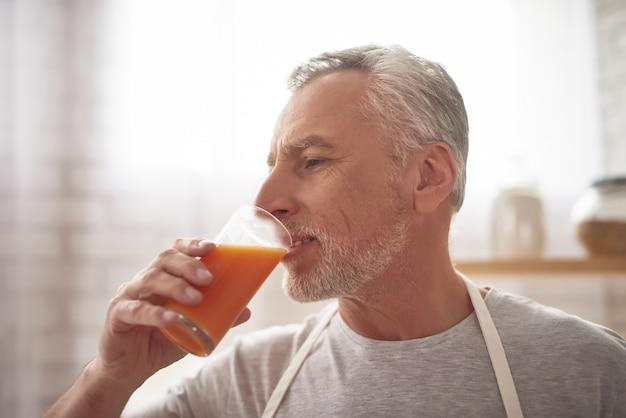 成熟した男は、絞りたてのオレンジジュースを飲みます。 Premium写真