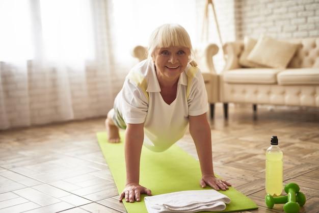 高齢者の女性は、ヨガを練習して板運動をしています。 Premium写真