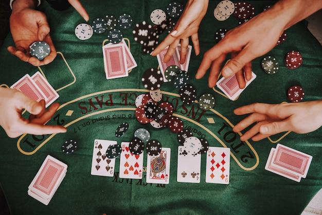 Молодая компания играет в холдем покер на вечеринке. Premium Фотографии