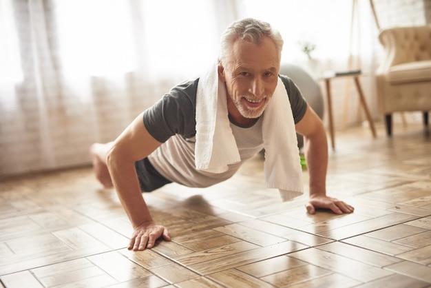 Счастливый старый спортсмен делает планку тренировки здравоохранения. Premium Фотографии