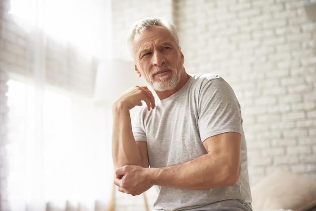 変形性関節症の肘の痛みに苦しんでいる老人。 Premium写真