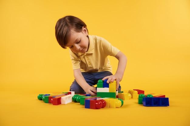 少年はプラスチックのおもちゃのレンガで遊ぶ。子供レジャーコンセプト。 Premium写真