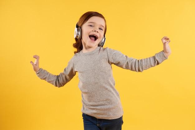 Жизнерадостная девушка с наушниками слушая к музыке. Premium Фотографии