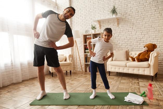 Отец и дочь делают упражнения на растяжку в домашних условиях. Premium Фотографии