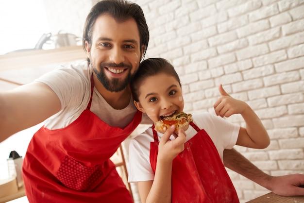 赤いエプロンのひげを生やした男と女は家族写真をやっています。 Premium写真
