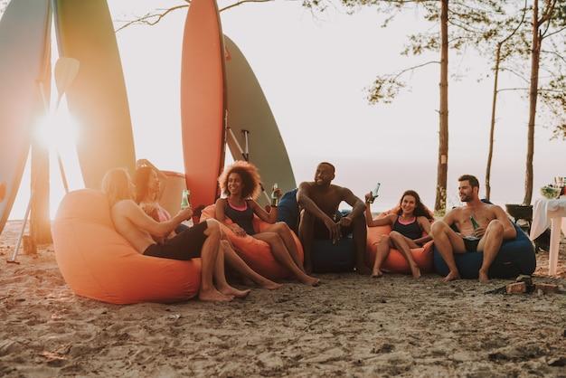 アフロマンはビーチで友達と休んでいます。 Premium写真