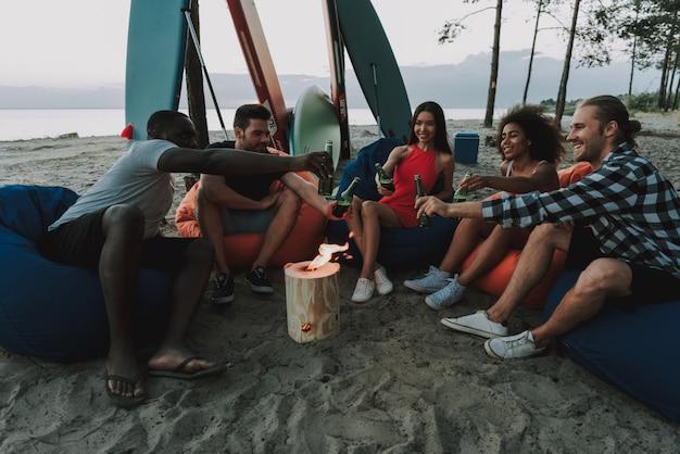 人々は燃えるログの周りのビーチで休んでいます。 Premium写真