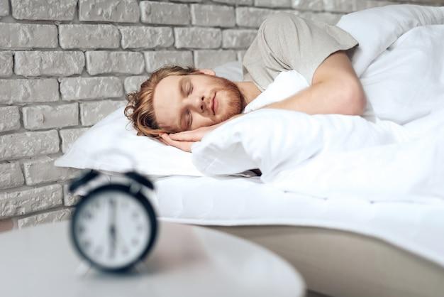 Рыжий молодой человек спит в спальне возле будильника. Premium Фотографии