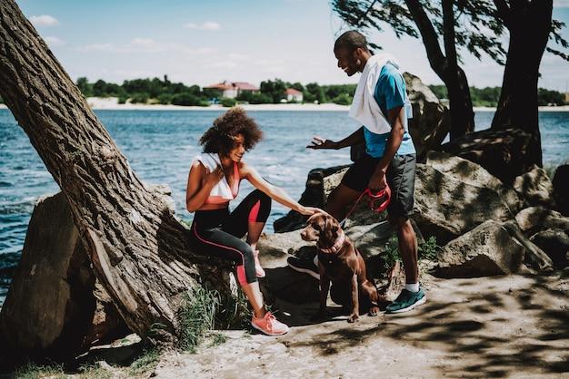 Афроамериканец пара на берегу реки с большой собакой Premium Фотографии