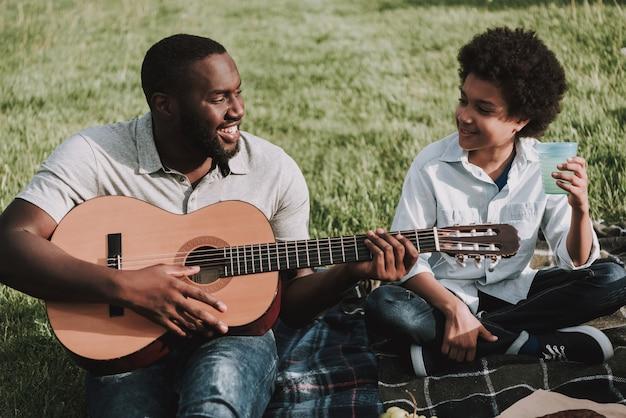 Отец играет на гитаре и смотрит на сына в пикник. Premium Фотографии