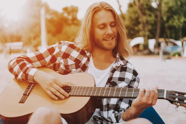 ビーチでギターを弾く長い髪の男ミュージシャン。 Premium写真