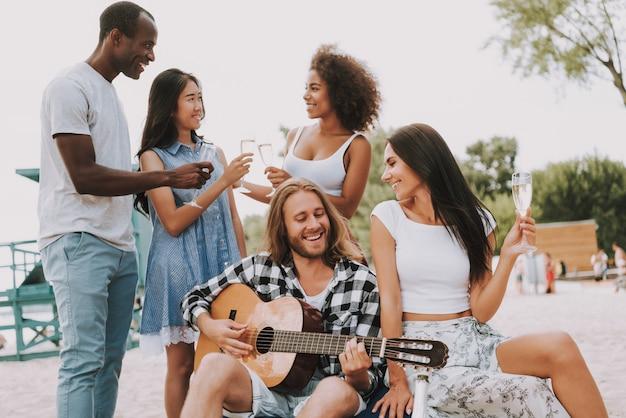 ギターを弾くビーチで祝う友達。 Premium写真