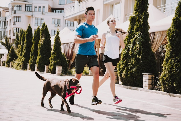 Пара бегает по дороге с большой собакой Premium Фотографии