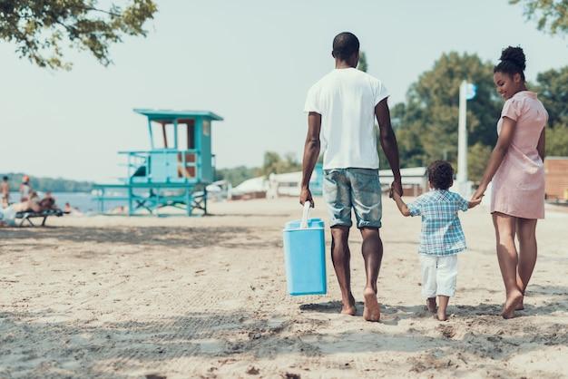 アフリカ系アメリカ人の家族は砂浜を歩いています。 Premium写真