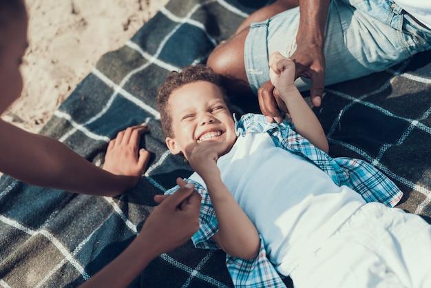 アフリカ系アメリカ人の家族は砂浜で毛布で休んでいます。 Premium写真
