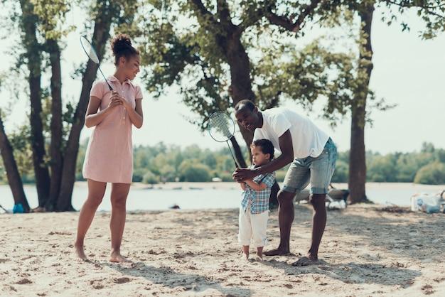 アフリカ系アメリカ人の家族は砂浜でテニスをしています。 Premium写真