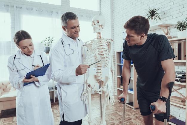 医師はスポーツマンを怪我する場所を示しています Premium写真
