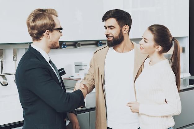 セールスマンのスーツと妻とのクライアントが握手しています。 Premium写真