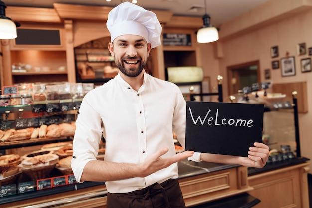 パン屋さんに立っているウェルカムサインを持つ若者 Premium写真