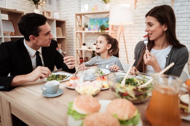 娘と両親がテーブルに集まった Premium写真