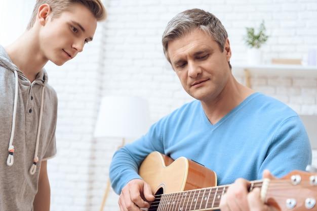 父はギターと息子で遊んでいます Premium写真