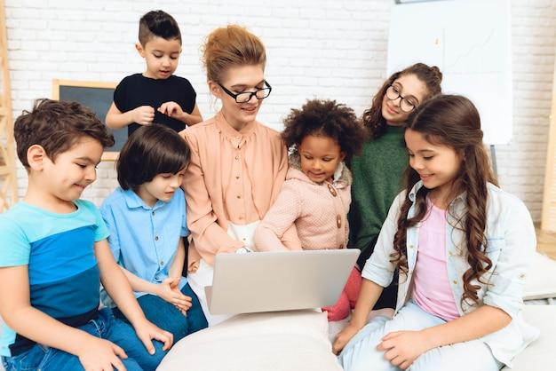 Симпатичная учительница сидит с детьми, которые смотрят на ноутбук. Premium Фотографии