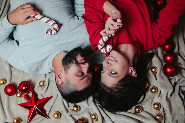 幸せな男と女はクリスマスツリーを飾る、男と女はキャンディーの杖を手に保持します。 Premium写真