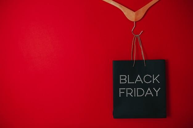 ブラックフライデーセールフラットレイアウト、ブラックフライデーバッグ、赤い表面のハンガー、 Premium写真