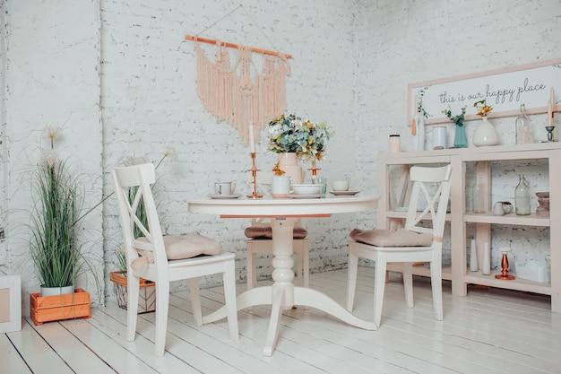 白いダイニングルームのインテリア。花、キャンドル、カップの白い丸いテーブル。 Premium写真