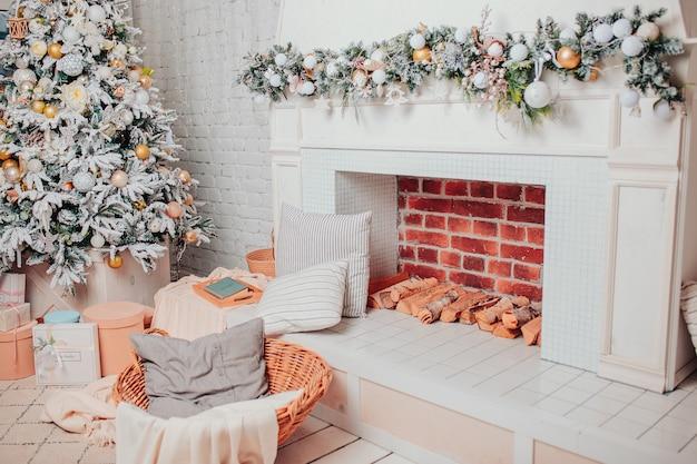 白い色のクリスマスインテリア。白い木の床、装飾品、ギフト、暖炉、バスケットとクリスマスツリー。クリスマスの心地よさ。 Premium写真