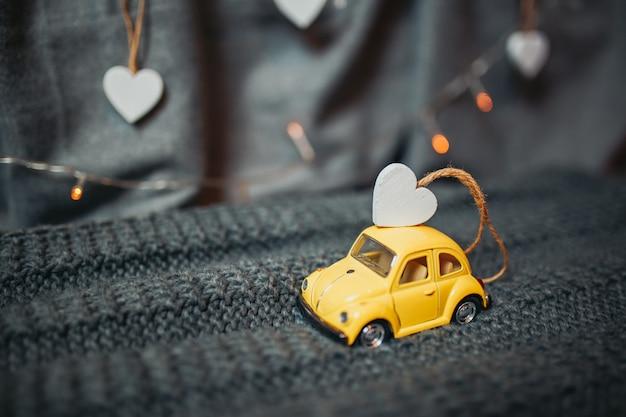 聖バレンタインの日カード。屋根の上に小さな木質心を持つ黄色のおもちゃの車。背景にガーランドライトとグッズ黄色のフォルクスワーゲンビートル。 Premium写真