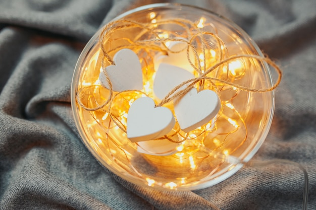 聖バレンタインの日カード。灰色の背景上にボウルにガーランドライトと白い木製の心。心と光のプレート。 Premium写真