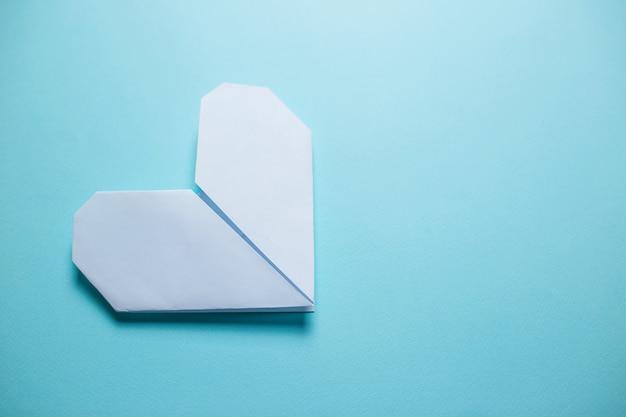 青の背景に白の折り紙の心。青の背景に聖バレンタインの日カード。 Premium写真