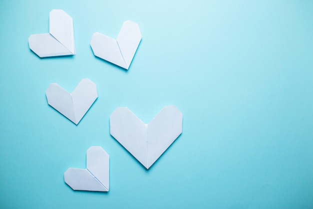 青の背景に多くの白い折り紙の心。青の背景に聖バレンタインの日カード。 Premium写真