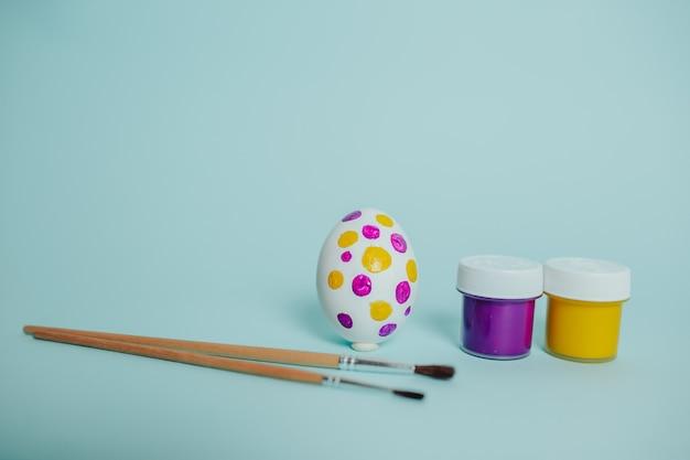 Разноцветные краски и кисти. процесс рисования пасхальных яиц. пунктирное пасхальное яйцо. Premium Фотографии