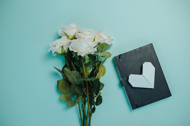 コピースペースを持つ春鮮度カード。緑の葉と白いバラ。長い茎を持つ美しい白いバラの花束。 Premium写真