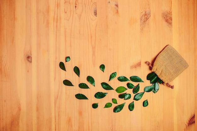 Зеленые листья на деревянных фоне. листья падают из сумки. Premium Фотографии