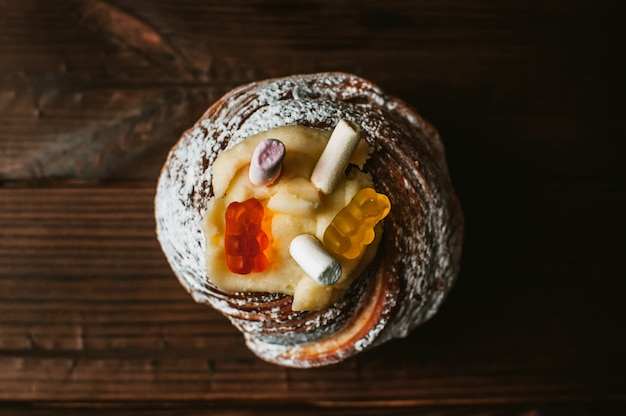 暗い素朴な木製の背景にマシュマロとゼリーのスタイリッシュなイースターケーキ。 Premium写真