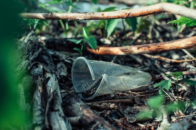 Пластиковый стаканчик и мусор в лесу. загрязнение окружающей среды. экологическая проблема и катастрофа. Premium Фотографии